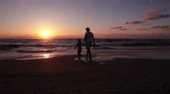 Daughter with her mother go to the sea and watching the sunset Stock Footage