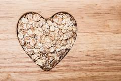 Oat cereal heart shaped on wooden surface. Stock Photos