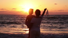 Mother and daughter go to the sea and watching the sunset. Stock Footage