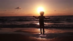 Little girl jumping on the beach at sunset. Stock Footage