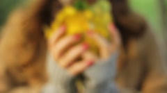 Girl holding a bouquet of yellow leaves in her hands and plays with it Stock Footage