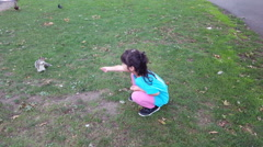 Girl feeding squirrel in the park. Girl play outdoors. Kid playing with pets Stock Footage