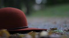 Modern maroon hat falling to the ground Stock Footage