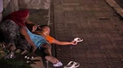 Beggars on the streets of Ubud. A poor child. Night Ubud. Stock Footage