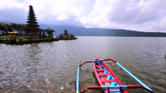 Water temple Pura Ulun Danu on a lake Beratan. Trimaran boat. Stock Footage