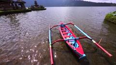 Water temple Pura Ulun Danu on a lake Beratan. Trimaran boat. Stock Footage