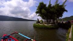 Water temple Pura Ulun Danu on a lake Beratan. Trimaran boat. Tourists Stock Footage
