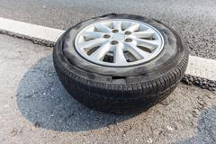 Broken tire damaged on surface putting on edge of road Stock Photos