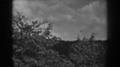 1938: view of a hill with many shrubs, few trees and a building WINCHESTER Stock Footage