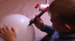 The Child Draws Using a Red Marker on a White Balloon. Stock Footage