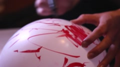 Girl Doing Mental Exercises. She Paints Using a Red Marker on a White Balloon. Stock Footage