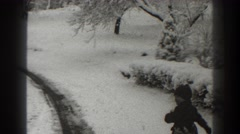 1938: child in dark outfit walks near tire track through snow-covered park  Stock Footage