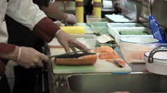 Process of cutting salmon for sushi rolls. Cook cutting up fish by knife Stock Footage