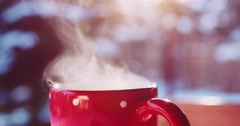 Steaming Cup of Hot Drink in Snowy Winter Morning. 4K DCi SLOW MOTION 120 fps. Stock Footage