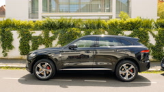 Jaguar F-Pace crossover parked in front of luxury house on summer day Stock Footage