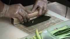 Process of making and cutting sushi rolls. Man rolling up sushi set Stock Footage