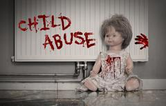 Concept of child abuse - Bloody doll Stock Photos