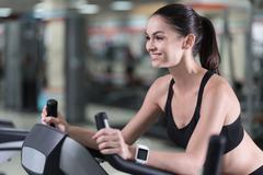 Smiling woman running on a treadmill Stock Photos