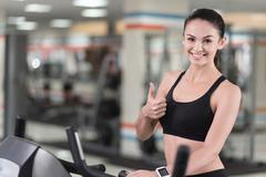 Active girl making an approving gesture with her thumb up Stock Photos