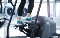 Legs in sneakers running on a treadmill Stock Photos