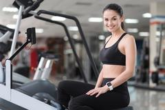 Smiling girl relaxing after workout in a gym Stock Photos