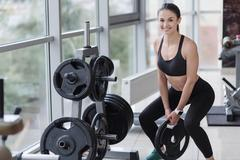 Active girl doing squatting exercises in a gym Stock Photos