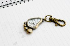Keyring - watch placed on the booknote. Old. Stock Photos