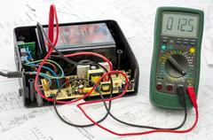 Testing old battery voltage with digital multimeter Stock Photos