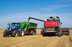 Harvest machine loading seeds in to trailer Stock Photos