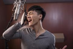 Young man singing in recording studio Stock Photos