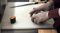 Process of making and cutting orange sushi rolls. Man rolling up sushi set Stock Footage
