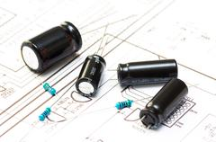 Several capacitors and resistors placed on the printed drawing Stock Photos