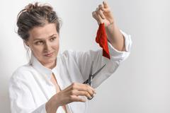 Woman  with old scissors and a small piece of red cloth Stock Photos