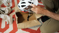Man unboxing new helmet strap for his bike helmet Stock Footage