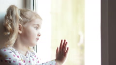 Little girl stares sadly out of a  window. Sitting on the window sill. The ch Stock Footage