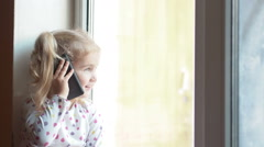 Blonde little girl talking on the phone. Sitting on the window sill. The chil Stock Footage