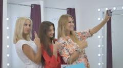 Three girls making selfie in dressing room in shop Stock Footage
