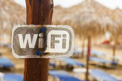 Wifi available zone sign on the beach,sunbeds and sunshades in the background Stock Photos
