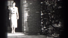 1938: woman walking out of her house in a pretty dress. CUMBERLAND MARYLAND Stock Footage