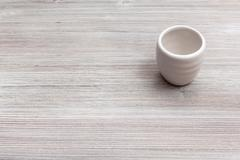 White cup for sake on gray brown wooden board Stock Photos