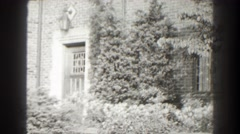 1938: pine and deciduous foliage sway in breeze outside a brick building  Stock Footage