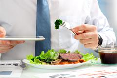 Man working on marketing strategy during business lunch, eating club steak Stock Photos