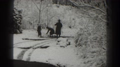 1938: two kids having fun in the snow while being looked after by an adult Stock Footage