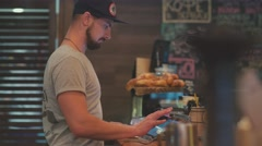 The bartender at the coffeehouse drives terminal. customer service Stock Footage