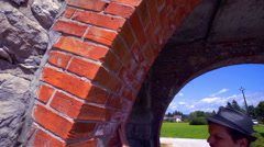Touching the arch made from red bricks and then driving away on a bike Stock Footage