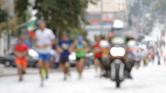 Motorcycle accompanies the runners in the marathon in blurred Stock Footage