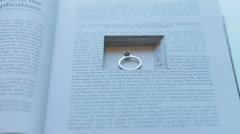 Engagement ring with diamont lies on book pages Stock Footage