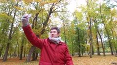 Man with smartphone taking video at autumn park Stock Footage