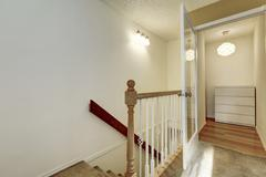 Upstairs hallway with staircase and ivory walls Stock Photos