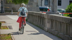 An old lady on a bike is crossing a bridge Stock Footage